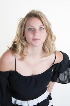 Blonde jonge vrouw met een zwart-witte jurk
