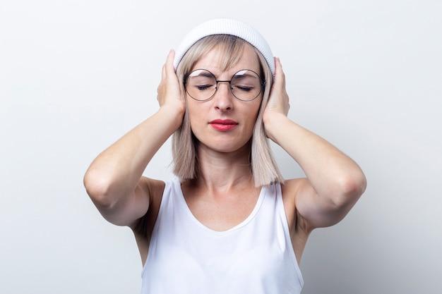 Blonde jonge vrouw met gesloten ogen, die haar oren bedekt met haar handpalmen op een lichte achtergrond. Premium Foto