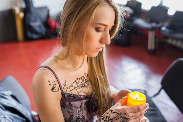 Blonde jonge vrouw met mehndiotatoegering op haar borst en hand die gele aangestoken kaars houden