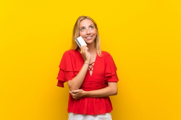 Blonde jonge vrouw over geïsoleerde gele muur die een creditcard houdt