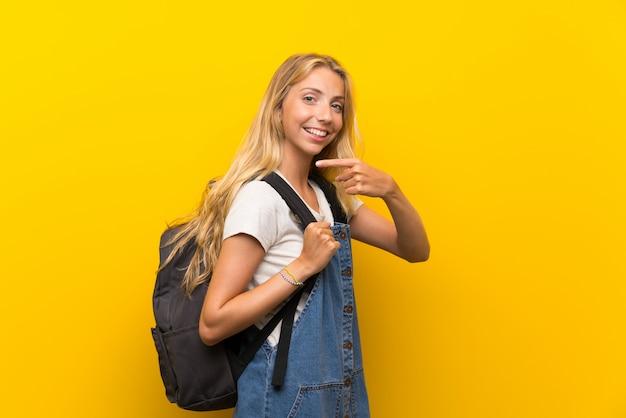 Blonde jonge vrouw over gele muur met rugzak