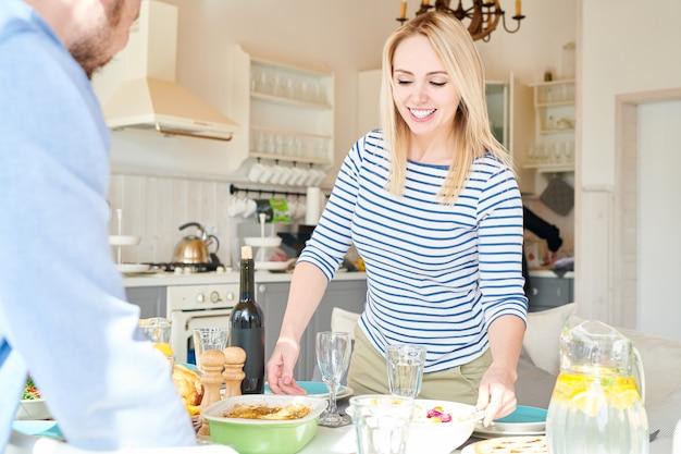 Blonde jonge vrouw tafel voor diner instellen