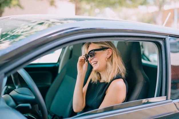 Blonde jonge vrouw zit in de auto lachen
