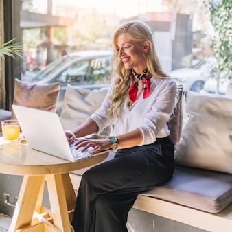 Blonde jonge vrouw zitten in de caf� met behulp van laptop