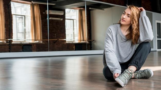 Blonde jonge vrouw, zittend op een hardhouten vloer voor spiegel