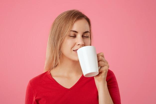 Blonde jonge vrouwelijke model geniet van aromatische drank uit witte kop, houdt de ogen gesloten, houdt van koffie of thee, heeft koffiepauze, geïsoleerde over roze. mensen en rust concept