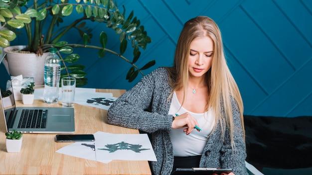 Blonde jonge vrouwelijke psycholoog die de rorschach inkblot test in bureau analyseren
