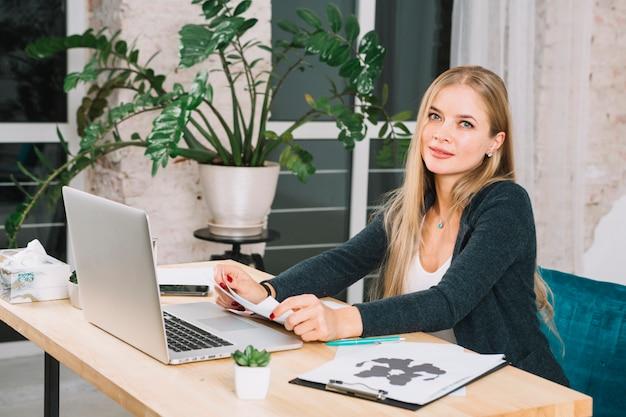 Blonde jonge vrouwelijke psycholoog in haar kantoor