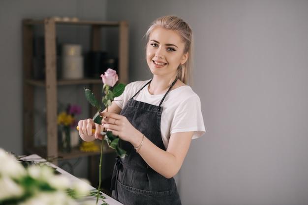 Blonde jonge vrouwenbloemist die schort draagt die verse roos tot boeket aan tafel voorbereidt