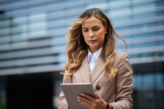 Blonde jonge zakenvrouw met behulp van een digitale tablet buiten