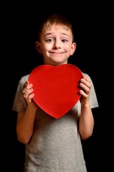 Blonde jongen die een rode doos in de vorm van een hart op zwarte houdt