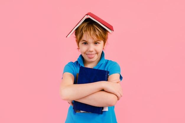 Blonde jongen die in t-shirt een boek leest dat dorstig is naar kennis over roze achtergrond.