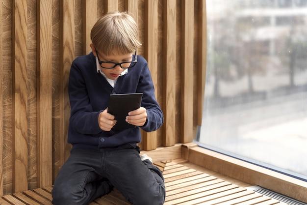 Blonde jongen die met een bril enthousiast de tabletcomputer bekijkt