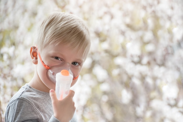 Blonde jongen in ademhalingsmaskerinhalator op bloeiende bomen.