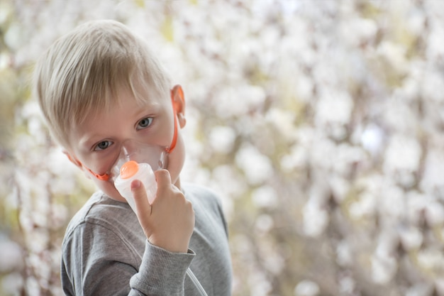 Blonde jongen in ademhalingsmaskerinhalator op een achtergrond van bloeiende bomen. thuisbehandeling. het voorkomen