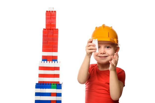 Blonde jongen in bouwhelm en rood t-shirt bouwt een wolkenkrabber op basis van de details van de ontwerper. isoleer op witte achtergrond.