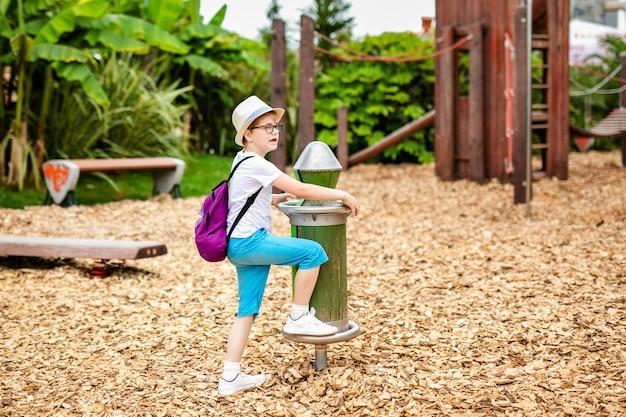 Blonde jongen in de strooien hoed en grote glazen in het amusementspark