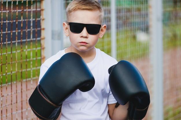 Blonde jongen in donkere bril en bokshandschoenen. hoge kwaliteit foto