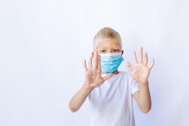 Blonde jongen in een beschermend masker en een wit t-shirt toont zijn handen met schuim