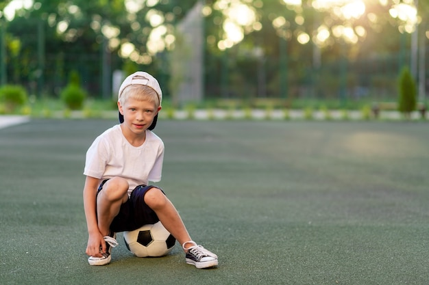 Blonde jongen in een pet in een sportuniform zit op een voetbal op het voetbalveld