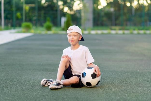 Blonde jongen in een pet in een sportuniform zit op een voetbalveld met een voetbal