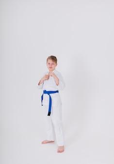 Blonde jongen in een witte kimono met een blauwe riem staat in een beschermende houding op een witte muur