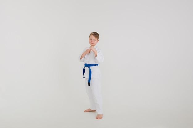 Blonde jongen in een witte kimono met een blauwe riem staat ter verdediging op een witte muur