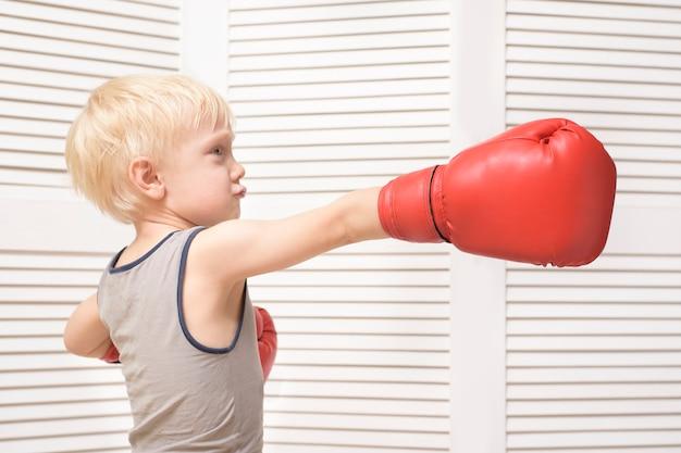 Blonde jongen in rode bokshandschoenen. opleiding. sport concept