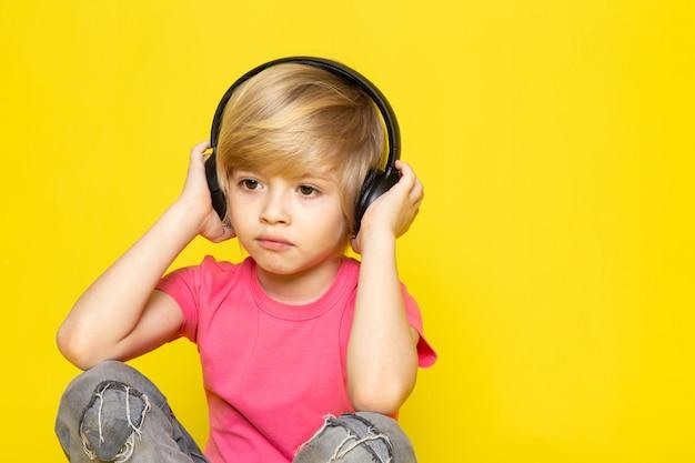 Blonde jongen in roze t-shirt en grijze spijkerbroek in zwarte koptelefoon luisteren naar muziek