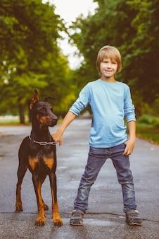 Blonde jongen knuffels met dobermann in zomer park