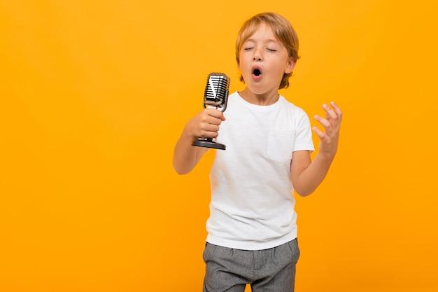 Blonde jongen met een microfoon op een oranje achtergrond