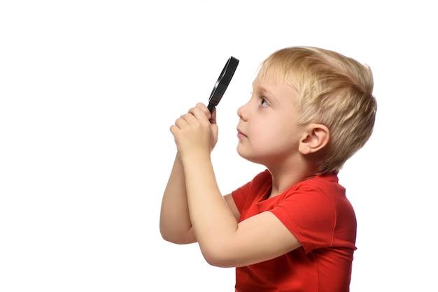 Blonde jongen met een vergrootglas in zijn handen. kleine ontdekkingsreiziger. witte achtergrond