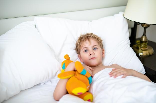 Blonde jongen met speelgoed oranje vos in het witte bed