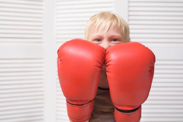 Blonde jongen wordt beschermd in twee bokshandschoenen. portret