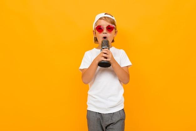 Blonde jongen zingt in een microfoon op een gele achtergrond.