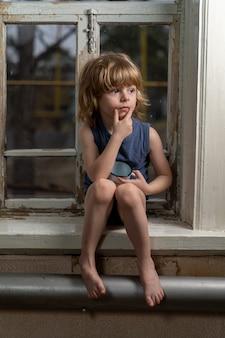 Blonde jongen zit op een armoedige houten vensterbank met een verwarde blik