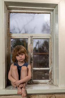 Blonde jongen zit op een raam met een houten gemeenschappelijke vensterbank