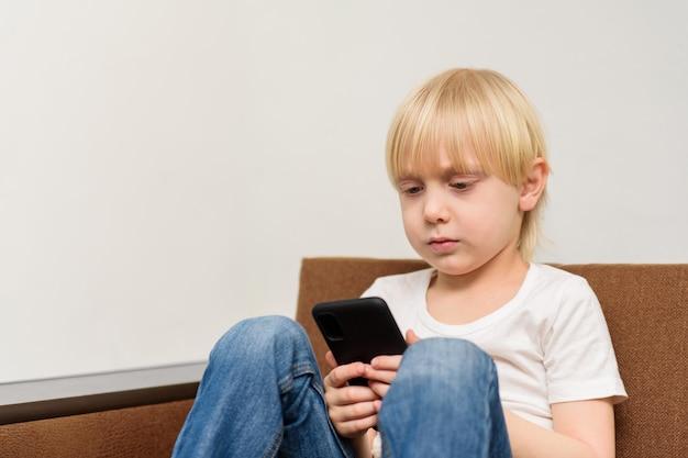 Blonde jongenszitting op bank en blikken in smartphone. apps voor kinderen
