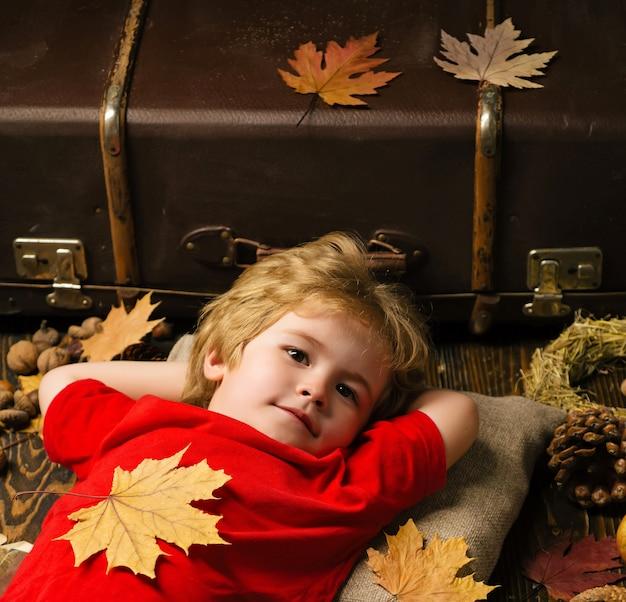 Blonde jongetje rusten met blad op buik ligt op houten vloer in herfstbladeren. kid spelen in