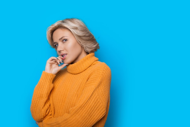 Blonde kaukasische charmante vrouw in een gele trui lippen aan te raken en poseren op een blauwe muur met vrije ruimte