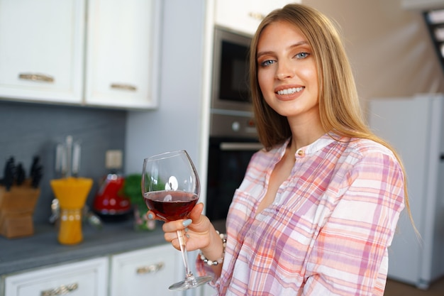 Blonde kaukasische gelukkige vrouw met glas rode wijn die zich in haar keuken bevindt
