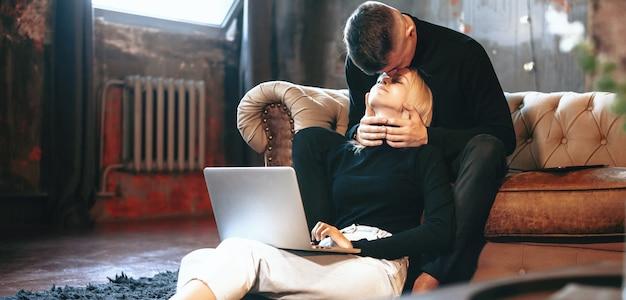 Blonde kaukasische vrouw die op de vloer met een computer werkt terwijl haar minnaar haar kust