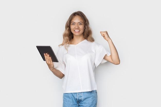 Blonde kaukasische vrouw die toothily op een witte muur glimlacht die het machtsteken gebaart en een tablet houdt