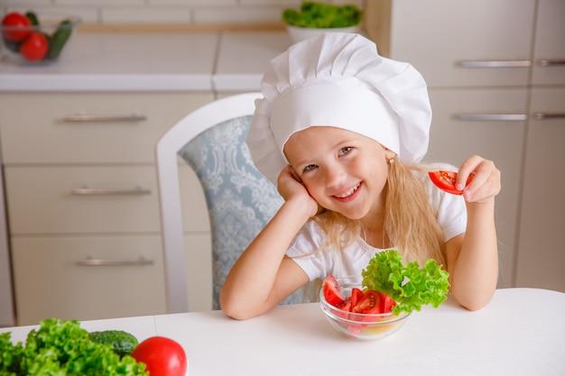 Blonde kind in de hoed van een chef-kok in de keuken groenten eten