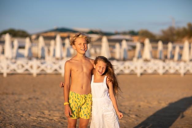 Blonde kinderen poseren op het strand. kopie ruimte