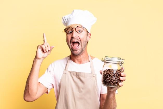 Blonde knappe chef-kok volwassen man met een fles koffiebonen