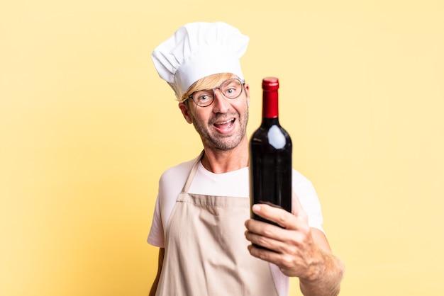 Blonde knappe chef-kok volwassen man met een fles wijn