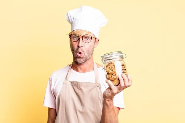 Blonde knappe chef-kok volwassen man met een fles zelfgemaakte koekjes