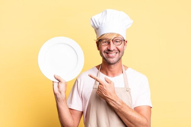 Blonde knappe chef-kok volwassen man met een lege schotel