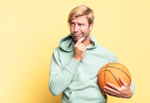 Blonde knappe volwassen man met een basketbalbal